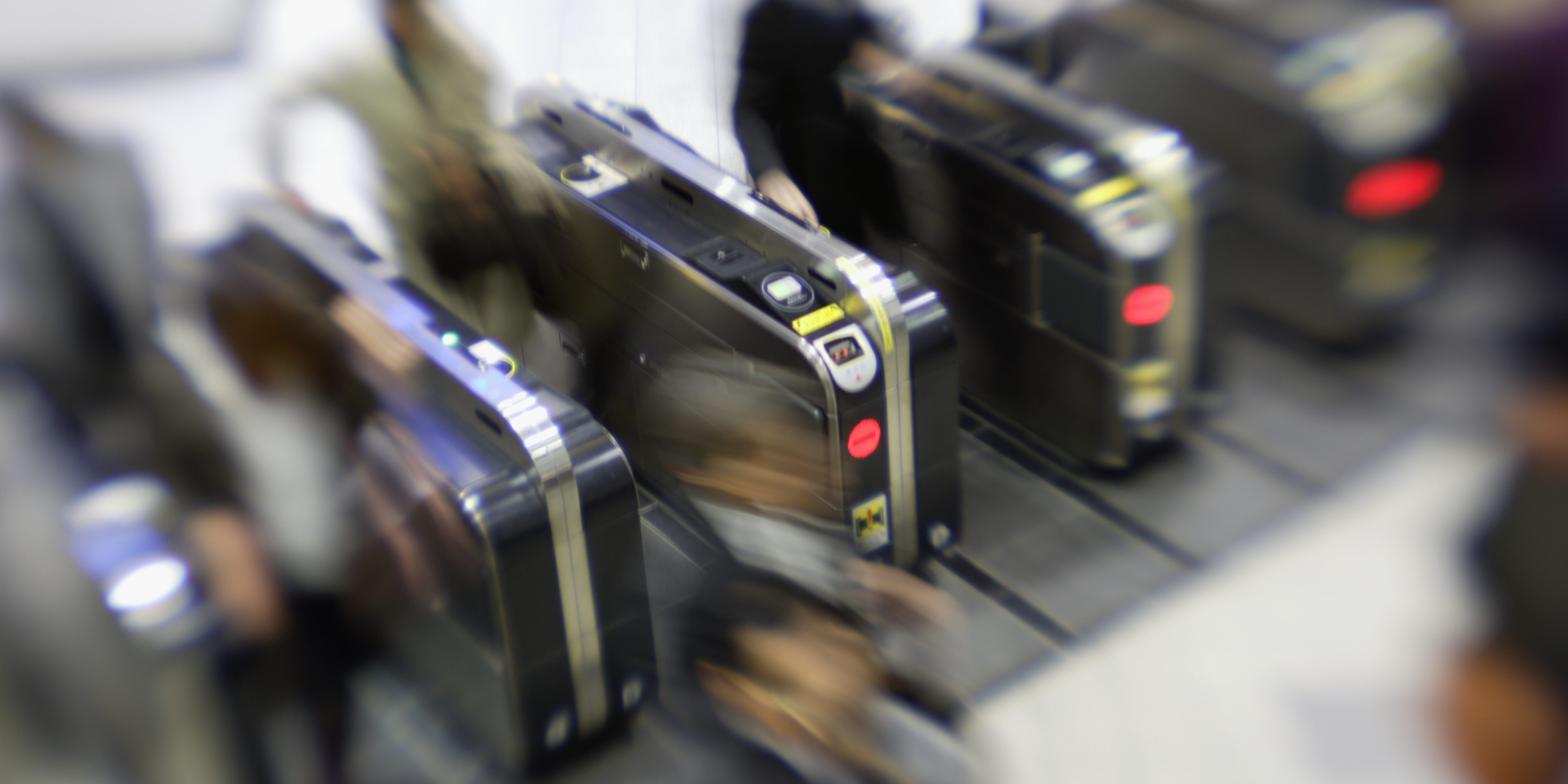 People passing through automatic ticket gate (blurred motion)
